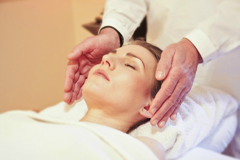 Woman Relaxes During a Reiki Treatment